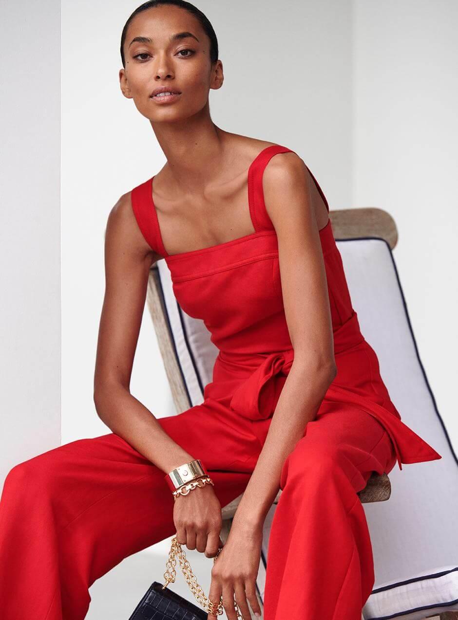 Woman wears red tie-waist jumpsuit.