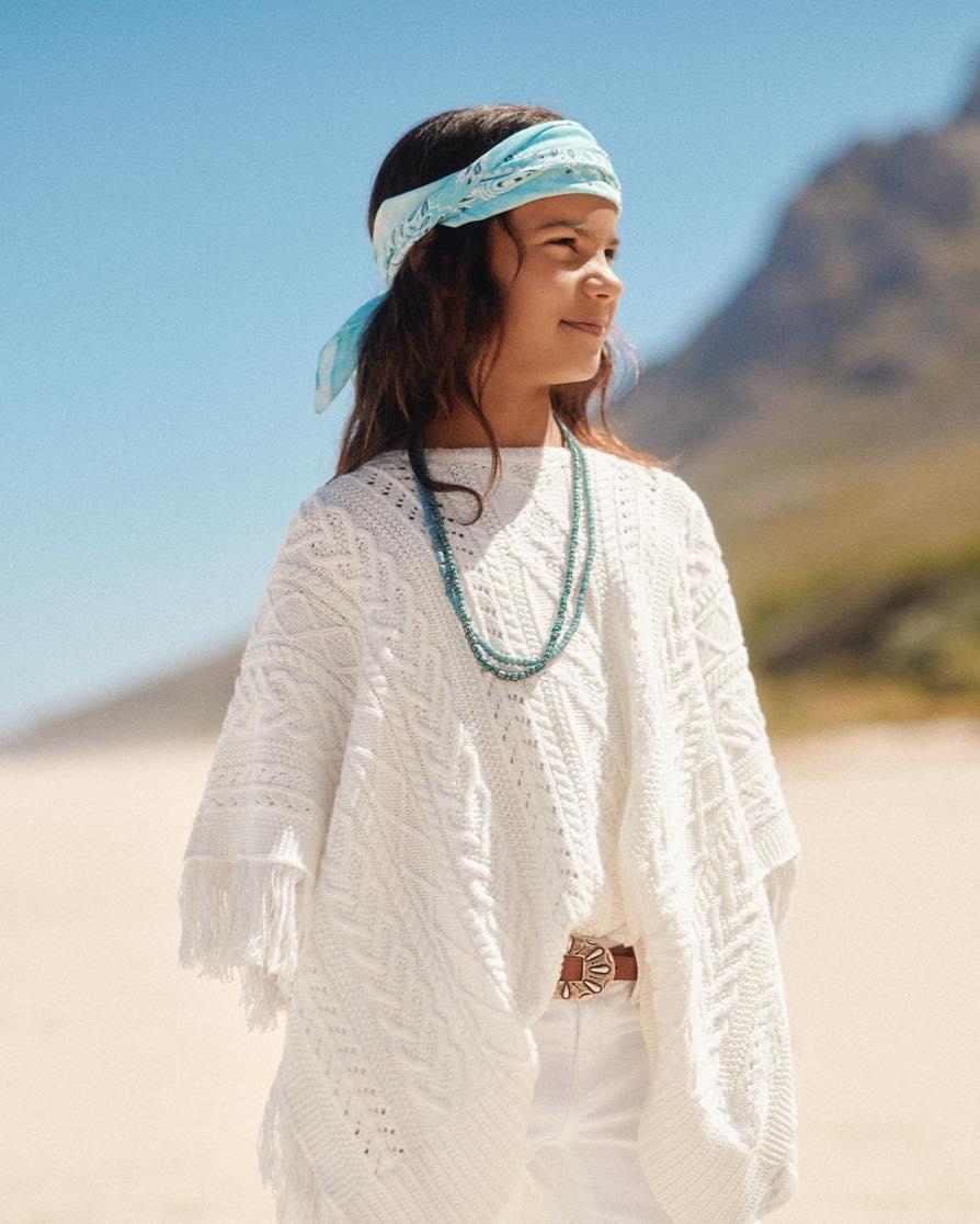 Girl in white fringe poncho & white pants
