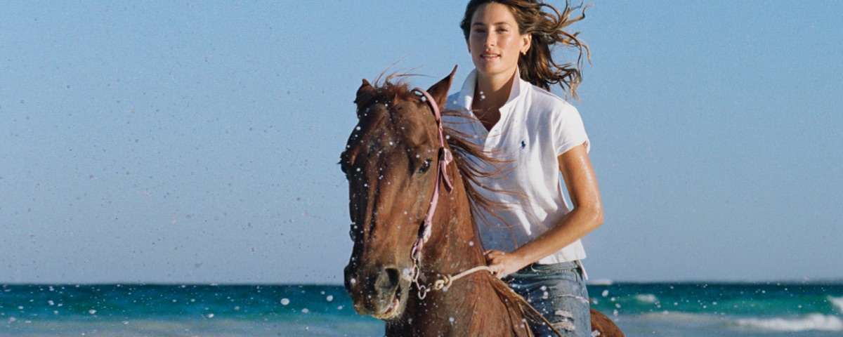 Woman in white Polo shirt & distressed jeans riding horse on beach
