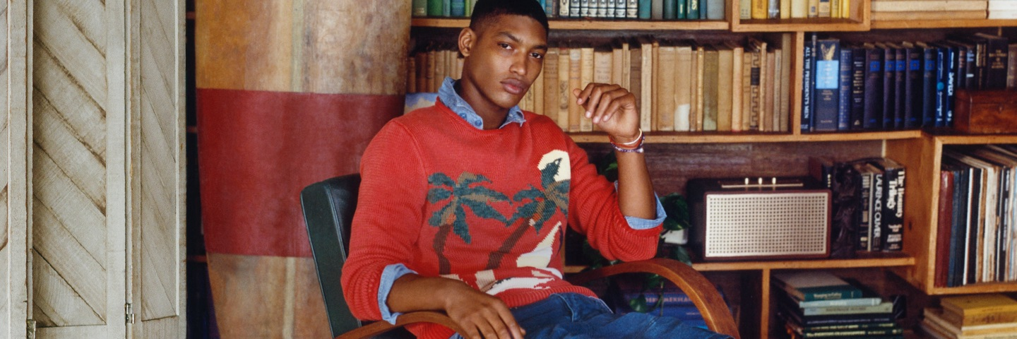 Man in orangey-red sweater with palm tree motif