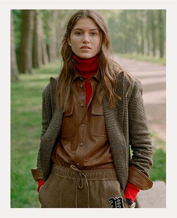 Woman wears tweed coat and beanie.