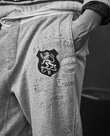 Close-up of grey sweatpants with crest patch at left thigh