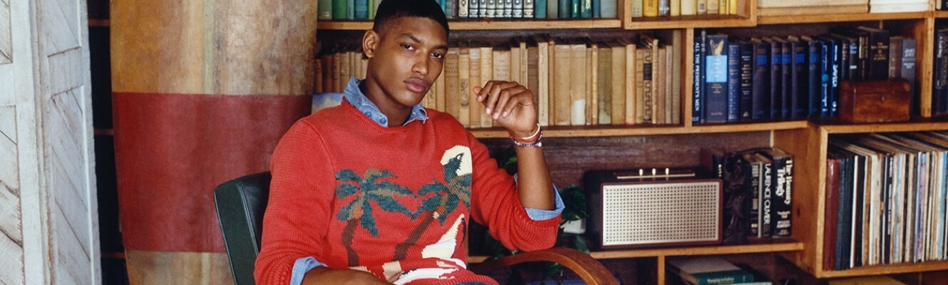 Man in orangey-red sweater with palm tree motif at front.