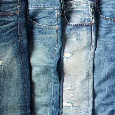Four pairs of jeans in a row with various washes