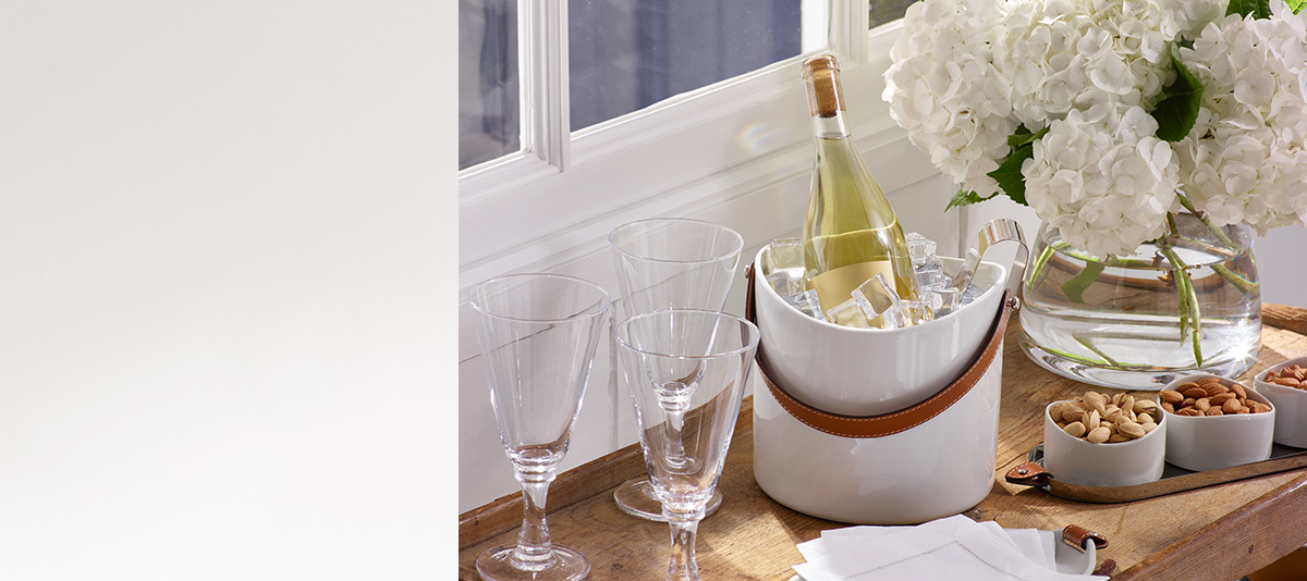 Wine bottle on ice next to flowers & bowls of nuts