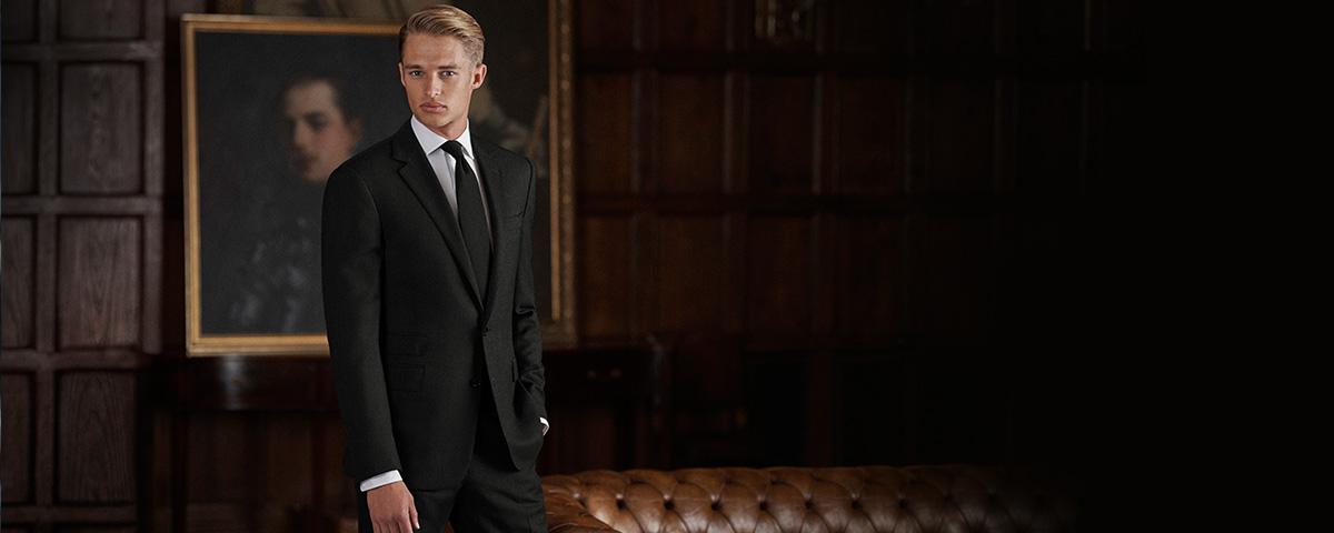 Model in sleek black suit in dark room