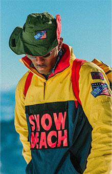 Model outdoors in Snow Beach yellow and navy color-blocked jacket