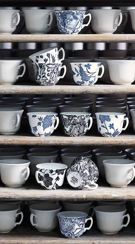 Shelves filled with floral-patterned mugs & plates with star motifs
