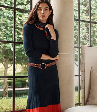 Woman wears navy outfit with orange accents.