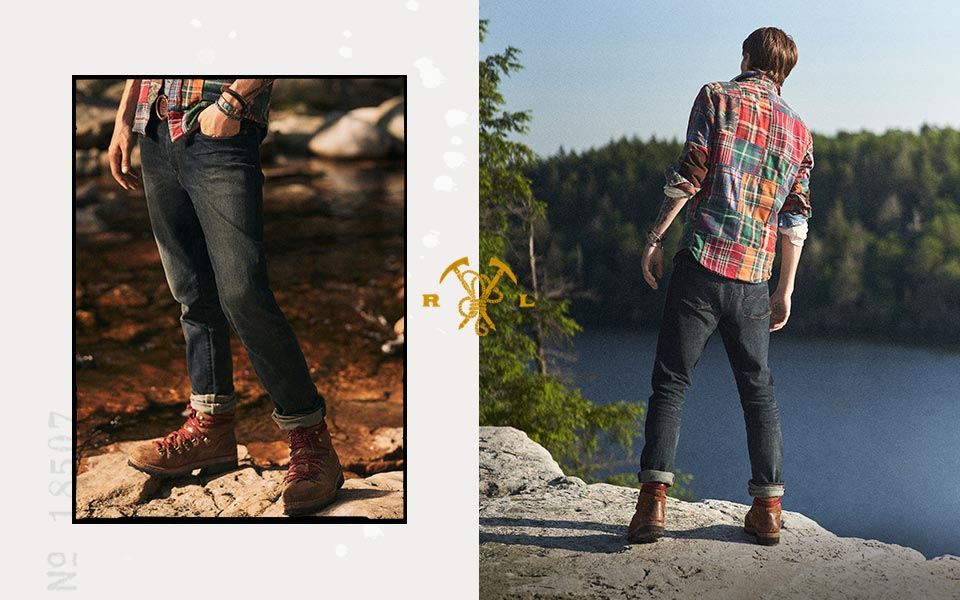 Man in plaid shirt & distressed jeans stands by lake